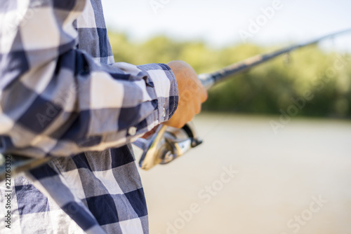 Fotografia  close up male hands catching fish with spinning on the river bank f