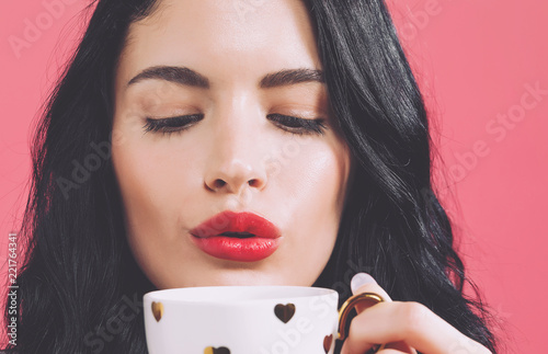 Obraz na plátne Young woman drinking coffee on a solid background