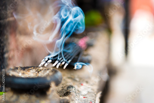Burning incense sticks as religious offerings at temple in Nepal. Incence sticks over blurred background.