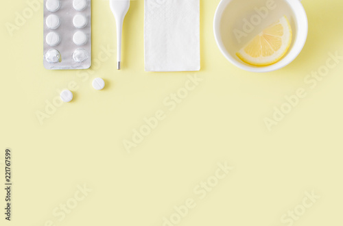 Fotografía Pills, thermometer and cup of tea on yellow background
