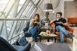 Leinwanddruck Bild - Asian couple sitting and eatting inn airport lounge when waiting the flight at modern international airport, travel and transportation concept