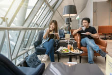Asian Couple Sitting And Eatting Inn Airport Lounge When Waiting The Flight At Modern International Airport, Travel And Transportation Concept