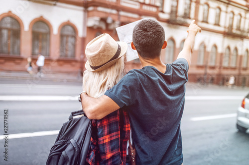 4b6524f105 Back view of woman with backpack and man embracing while holding map and  pointing away on street
