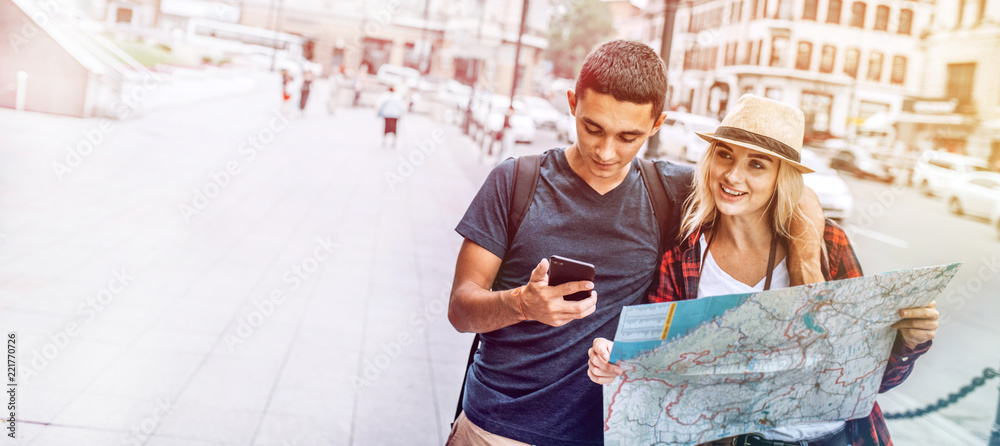 Fototapeta Casual young man and woman with map using phone on street exploring city while traveling