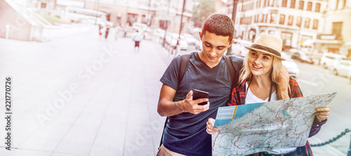 Fotografia  Casual young man and woman with map using phone on street exploring city while t