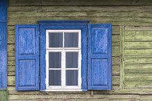 Old Weathered White Window With Blue Shutters On Green Wooden Wall