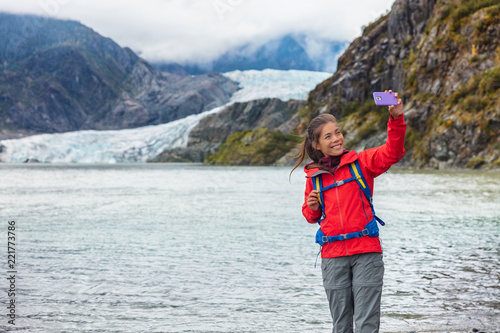 fototapeta na drzwi i meble Tourist woman taking selfie photo at Mendenhall glacier in Juneau, Alaska. Famous tourism destination on Alaska cruise, USA travel.