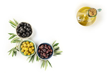 Overhead Photo Of Various Olives In Bowls And A Cruet Of Olive Oil On White With Copy Space