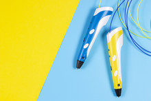 3d Pens With Colourful Plastic Filament On Blue And Yellow Background.