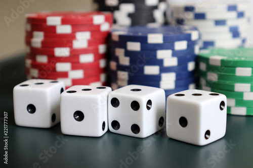 фотография  Casino chips and dice on the dark green background.