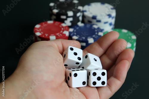 Foto  A woman's hand holding dice with a pile of casinos chips.