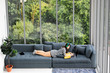 Asian woman laying on sofa near big glass wondows, relaxing alone in house with green forest in background