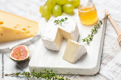 Brie or camembert cheese on white wooden board served with honey, green grapes and figs