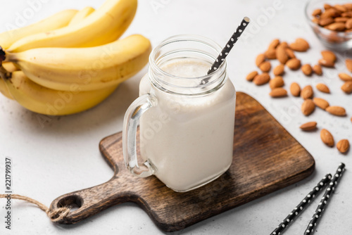 Banana protein smoothie in drinking glass on wooden serving board. Closeup view