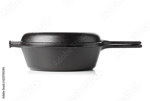 Empty, clean black cast iron pan or dutch oven side view over white