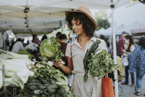 Fotografia, Obraz Beautiful woman buying kale at a farmers market