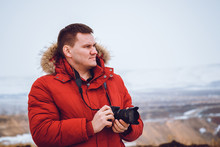 A Man In A Red Down Jacket With A Camera Travels To The Mountains In Winter