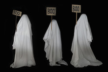Three People Disguised As Ghosts With A White Sheet
