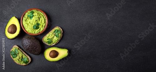 Mexican Dip Sauce Guacamole with avocado  in a clay bowl  on black background. Avocado spread. Top view. Copyspace.