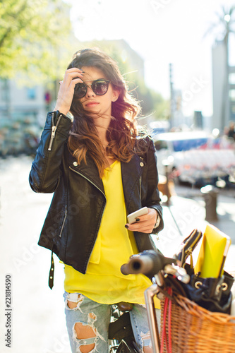 Fotografie, Obraz  Pretty girl in sunglasses posing to camera on bike on street in sunny morning