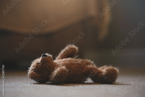 Teddy bear is laying down on carpet in retro filter, Lonely teddy bear laying down alone in living room at night ,lonely concept, international missing children's day.