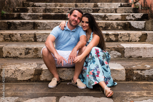 Fotografie, Obraz  embracing couple sitting on the stairs looking at the camera.