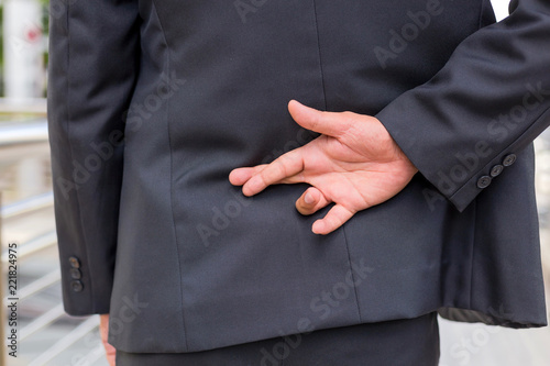 Fényképezés businessman telling lies, hold crossed finger his back with modern building back