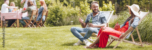 Horizontal photo of two friends talking and sitting on sunbeds in a garden