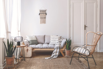 Fototapeta Armchair near beige sofa with pillows in living room interior with plants and door. Real photo
