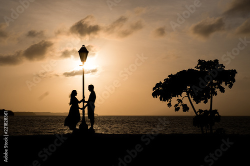 Foto op Aluminium Jacht Silhouette of a couple in a lamp over a wall at sunset in Sao Luis do Maranhao.