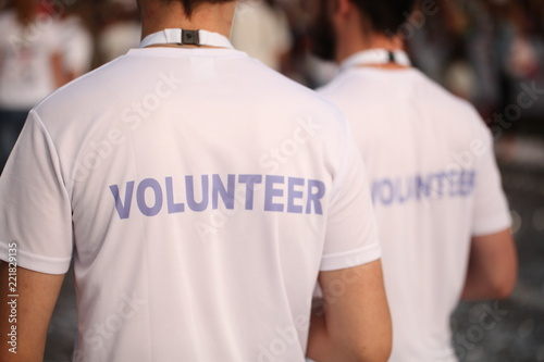 Obraz Men in T-shirts with the inscription Volunteers at a sporting public mass event competition - fototapety do salonu
