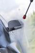 Mann nutz Hochdruckstrahler mit Wasser um Reinigungsmittel bei Autowäsche in Auto SB Waschbox abwaschen