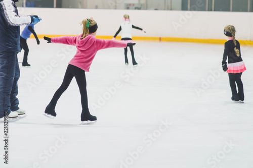 Fototapeta Little girls learning to ice skate