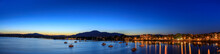 Magog Town At Night In Reflections Of Memphremagog Lake. Canadian Romantic Landscape With Mountains, Lake, Night Sky And Awesome Water Background.