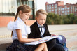 Two of happy little school children boy and girl reading book outdoor