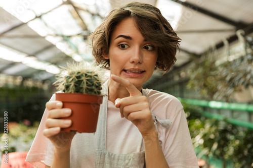 Papiers peints Cactus Woman gardener standing over flowers plants in greenhouse holding cactus