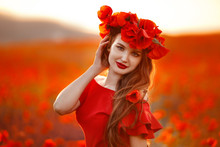 Beautiful Girl In Red Poppy Field At Sunset. Beuaty Makeup. Free Happy Woman Enjoying Nature. Beauty Female Outdoor Portrait. Freedom Concept. Enjoyment.