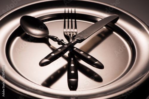 Fotografia  close-up view of cutlery arranged on shiny metal tray on grey