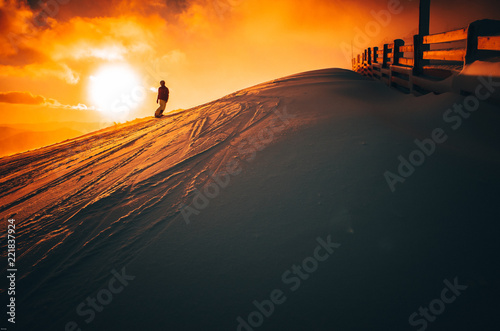 Silhouette of snowboarder in ski resort, Colorful sunset in background, edit space