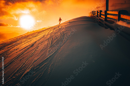 Snowboarder in ski resort. Winter sport photo. Orange sunset light in background. Edit space