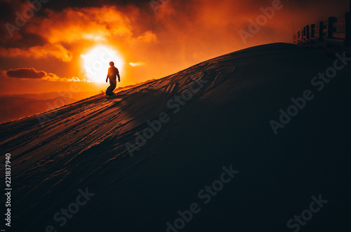 Poster Wintersporten Snowboarder in ski resort. Winter sport photo. Orange sunset light in background. Edit space. Christmas and New Year time, snowy photo, edit space