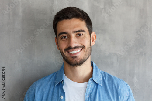 Fotografía  Closeup headshot of young handsome European Caucasian male isolated on grey back