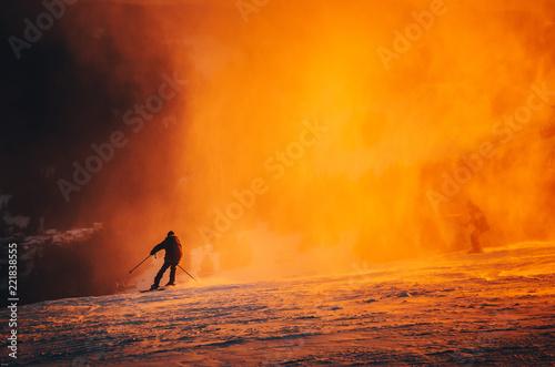 Wall Murals Magenta Skier in ski resort - orange sport photo, colorful winter sunset light