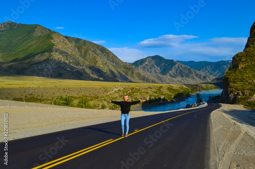 Young pretty blonde woman on a black asphalt road with yellow markings and sand Canvas Print