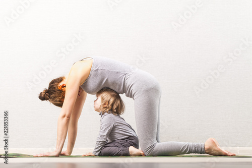 mother doing gymnastics yoga with baby. developing classes at home with a child. healthy lifestyle. Mom and baby doing physical culture