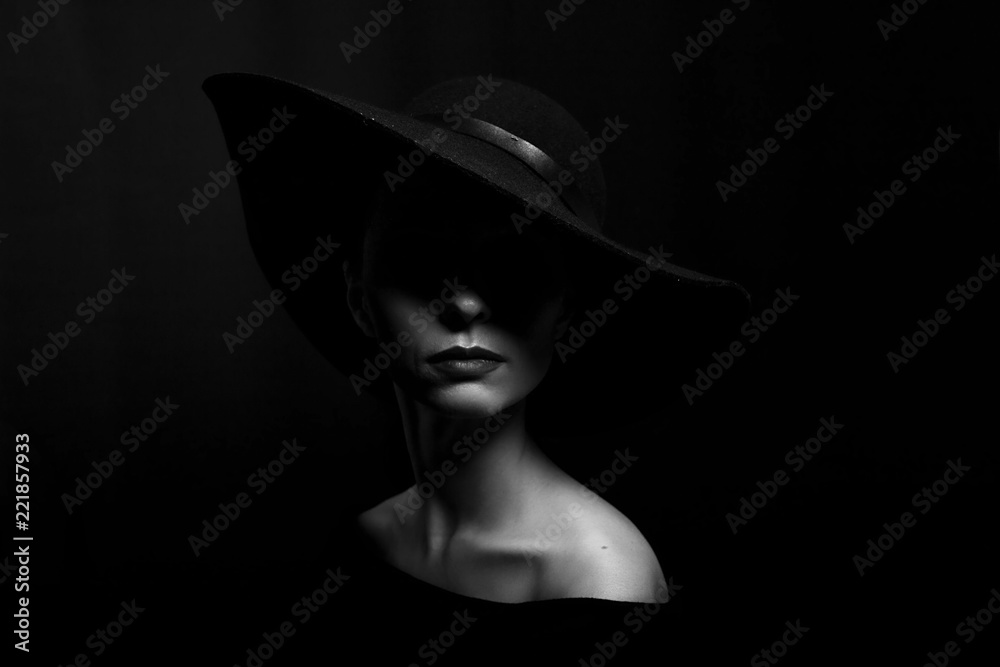 Fototapeta portrait of a woman in a black hat on a black background black and white photo