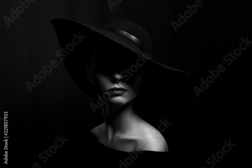 Obraz portrait of a woman in a black hat on a black background black and white photo - fototapety do salonu