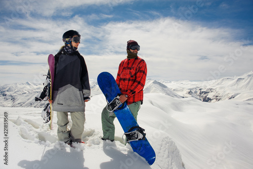 guy and a girl in warm clothes stand with snowboards against the mountain snow tops