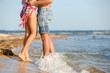 Young couple spending time together on beach, focus on legs