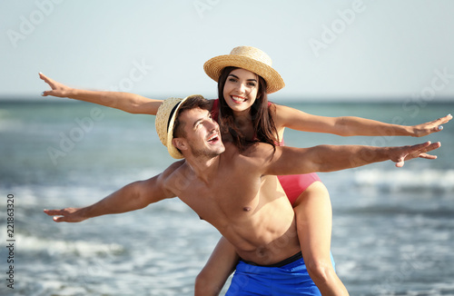 Happy young couple having fun at beach on sunny day